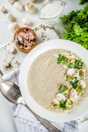 Mushroom champignon cream soup in a bowl with parsley, white marble background copy space