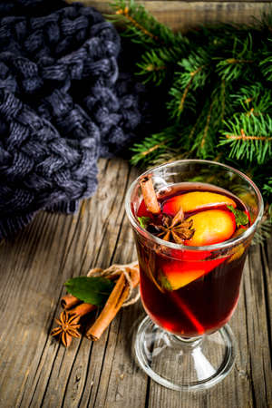 Classic winter autumn hot drink, mulled wine cocktail with  spices, with plaid and Christmas tree branches, on a wooden background, copy space for text