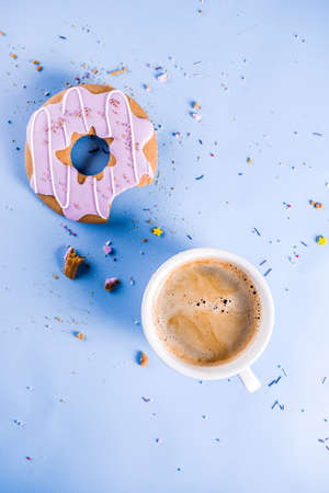 Rest and relaxation concept, coffee cup and biscuits donut with sugar coating, with a notepad for notes or wishes on a bright trendy background, top view space for text Imagens