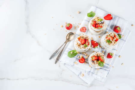 Healthy summer breakfast idea, homemade layered parfe dessert in small jar with granola, yoghurt and strawberry, dark background copy space above Stock Photo