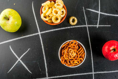 Tic tac toe healthy and unhealthy snack concept with crackers, chips and apples on black chalkboard Stok Fotoğraf - 106171255