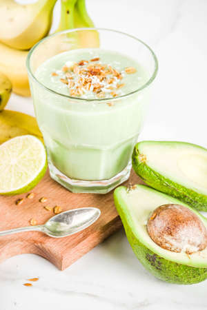 Healthy summer drink, avocado and banana smoothie with lime, granola and coconut milk, dark rusty background copy space Stock Photo - 106171377