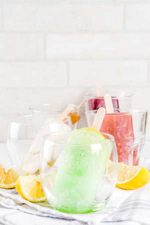 Summer party food ideas, frozen boozy alcohol cocktails popsicles - Prosecco, Vodka lime mojito, Champagne, Bellini, Margarita, Negroni etc white marble table copy space Stock Photo - 106171382
