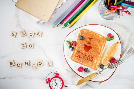 Back to school kids breakfast concept, pancakes with raspberry jam - I love school, on white marble stole, with books, alarm clock, pencils, school supplies. Top view copy space