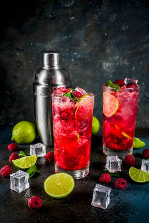 Iced summer drink cocktail, Raspberry and lime lemonade with fresh mint and lime, dark blue rusty background copy space Stockfoto