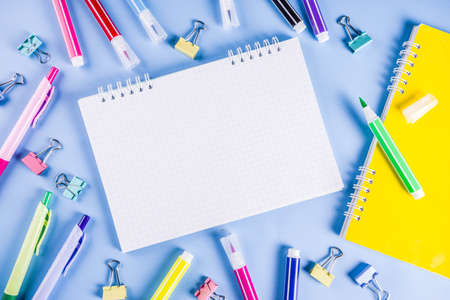Back to school background, with bright accessories supplies for school and study - pen, pencils, markers, pencils, rulers, paperclips, sticks, notebooks. On a light blue background, top view, free copy space for text Banco de Imagens
