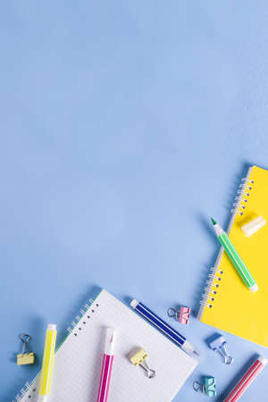 Back to school background, with bright accessories supplies for school and study - pen, pencils, markers, pencils, rulers, paperclips, sticks, notebooks. On a light blue background, top view, free cop