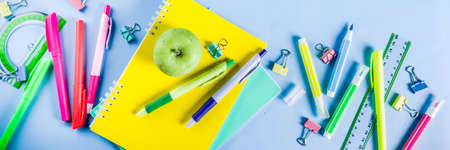 Back to school background, with bright accessories supplies for school and study - pen, pencils, markers, pencils, rulers, paperclips, sticks, notebooks. On a light blue background, top view, free copy space for text Imagens