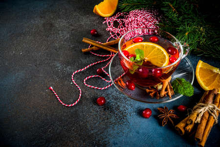 Autumn winter hot drink, cranberry spicy tea with orange, cinnamon and anise. On an old wooden background, with christmas tree branches, copy space for text Archivio Fotografico - 106382057