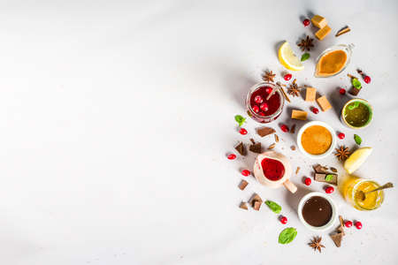 Various sweet sauces, toppings and syrups - lemon, orange, caramel, chocolate, cranberry, cherry, blueberry, on a light concrete background, top view copy space for text