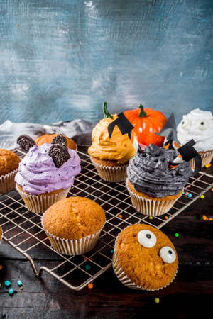 Funny childrens treats for Halloween: variations of cupcakes, decorated in the form of different monsters, witches, pumpkins, ghosts. Cooking process. On a wooden table, copy space for text, top view Stock Photo