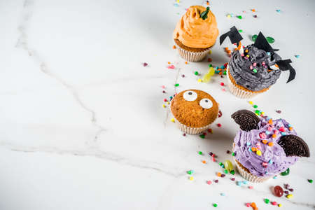 Funny childrens treats for Halloween: variations of cupcakes, decorated in the form of different monsters, witches, pumpkins, ghosts. White marble background copy space for text, Stock Photo
