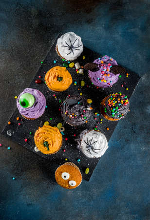 Funny childrens treats for Halloween: variations of cupcakes, decorated in the form of different monsters, witches, pumpkins, ghosts. Dark rusty blue background copy space for text, top view