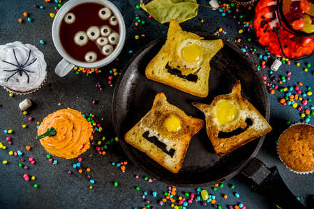 Funny childrens treats for Halloween, an idea for a festive breakfast. Sandwiches toast with eggs, looking like creepy monsters, hot chocolate with marshmallow eyes and funny monster cupcakes.