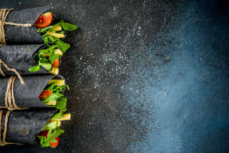 Trendy healthy vegan food. Black charcoal wrapped sandwiches, with fresh vegetables, cheese, on a dark blue background, space for text
