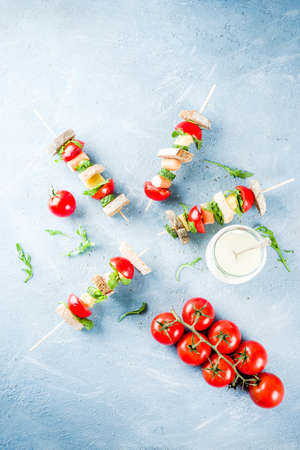 Healthy summer snack idea, salad sandwiches kebab on skewers, with bread slices, tomato, greens, cucumber, cheese, sausages, with yoghurt dipping, on light concrete background copy space top view