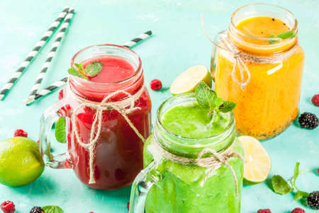 Healthy fresh fruit and veggie smoothies with ingredients on light blue concrete table, copy space