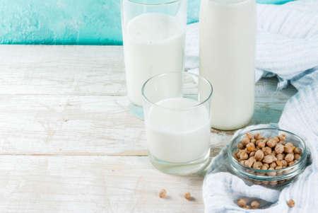 Vegan alternative food, soy non-dairy milk on light blue background, copy space