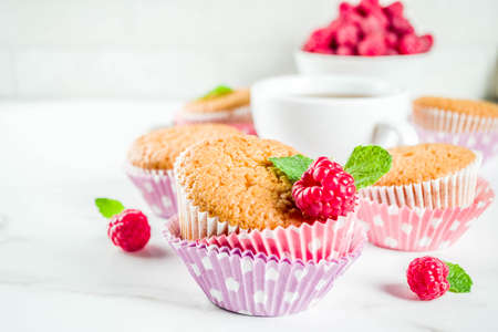 Sweet summer dessert, homemade baked muffin with raspberry jam, served with tea, fresh raspberries and mint. On a white marble table, copy space Stok Fotoğraf
