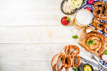 Oktoberfest food menu, bavarian sausages with pretzels, mashed potato, sauerkraut, beer bottle and mug, white wooden background copy space top view