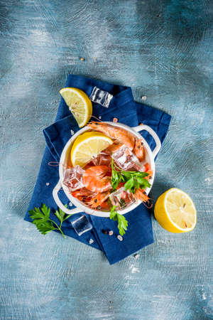 Seafood, boiled shrimps with lemon and ice on a light blue background