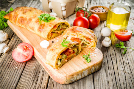 Vegetable savory strudel, homemade autumn baking, with tomatoes, bell pepper, mushrooms, wooden background copy space