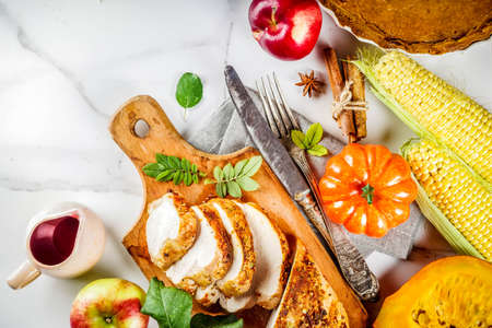 Thanksgiving holiday table with traditional festive food - turkey, pumpkin pie, pumpkins, green beans, cranberry sauce, corn, autumn apples, white marble table, top view copy space for text