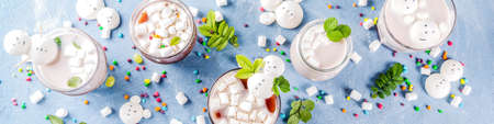 Variations of bitter and dairy hot chocolate with funny marshmallow in form snowmen, white bears, with sweets and decorative leaves, light blue background, top view copy space banner