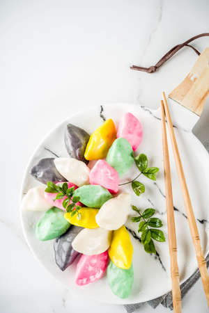 Traditional Chuseok day food, Korean Half-moon Shaped Rice Cake Songpyeon, white marble background copy space top view