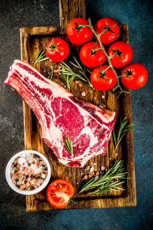 Raw rib eye beef steak meat with spices and ingredients for cooking dark rusty background copy space top view Stock Photo