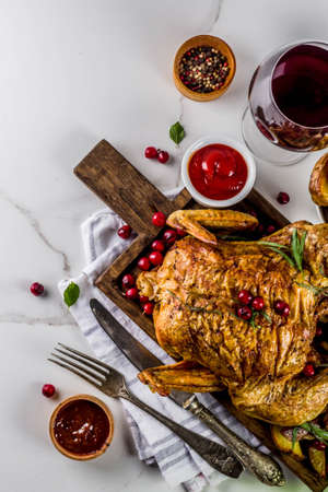 Christmas, thanksgiving food, baked roasted chicken with cranberry and herbs, served with fried vegetables, fresh berries wine and sauces on white marble table, copy space top view