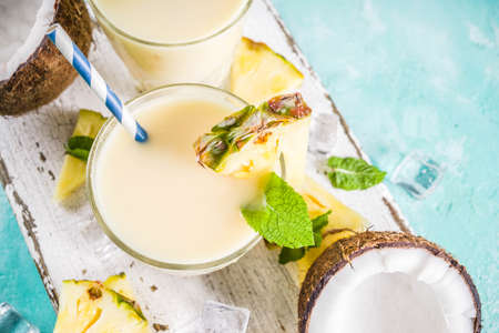 Refreshing summer drink, homemade pina colada cocktail, on a light blue background, with pieces of pineapple, coconut, ice and mint leaves, copy space top view