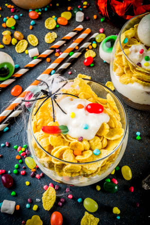 Funny Halloween food ideas, trifle dessert for kids, with spooky Halloween decorations and candies, dark background