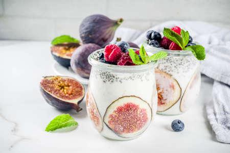 Healthy detox breakfast appetizer - yoghurt smoothie or milkshake with figs, blueberries, raspberries chia seeds, white marble background, copy space
