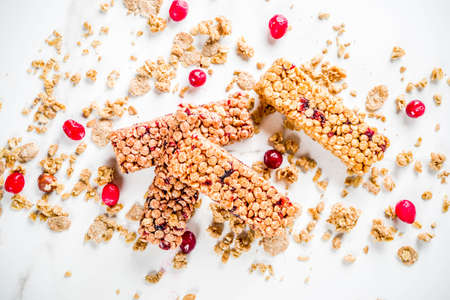 Multi grain granola muesli bar. Healthy sweet food, diet snack, with dried berries, nuts, cereals and honey. On a white marble background, top view copy place for text.