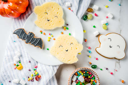 Kids breakfast or snack idea, funny ghost sandwiches for Halloween, with cheese and edible marker painting, white background copy space top view Stock Photo