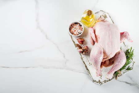 Raw whole chicken ready for cooking white marble background copy space