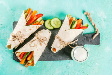 Summer healthy snack, Mexican style tortilla sandwich wraps assorted colorful fresh vegetable sticks (celery, rhubarb, pepper, cucumber and carrot) with yoghurt sauce dip light blue background