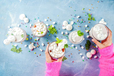 Girl drinks hot chocolate with funny marshmallow in form snowmen, white bears, with sweets and decorative leaves, light blue background, top view copy space, hands in picture