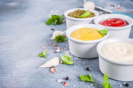 Set of four classic sauces - ketchup, mayonnaise, mustard, pesto - with herbs and spices. Blue concrete background top view copy space Banque d'images - 107745253