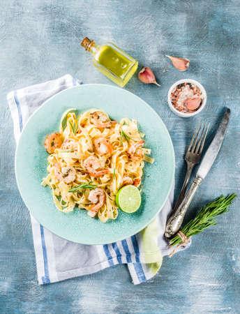 Cibo italiano, fettuccine classiche con gamberetti e salsa cremosa, olio d'oliva, lime ed erbe aromatiche, vista dall'alto di spazio copia tavolo azzurro