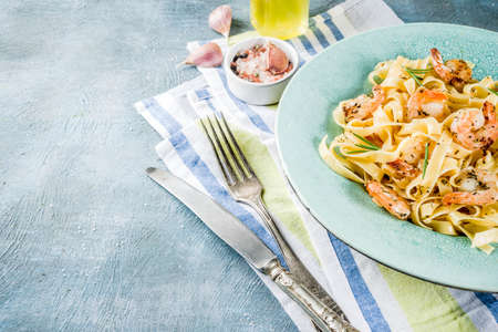 Italian food, classic fettuccine pasta with shrimp and creamy sauce, olive oil, lime and herbs, light blue table copy space Archivio Fotografico - 107778831