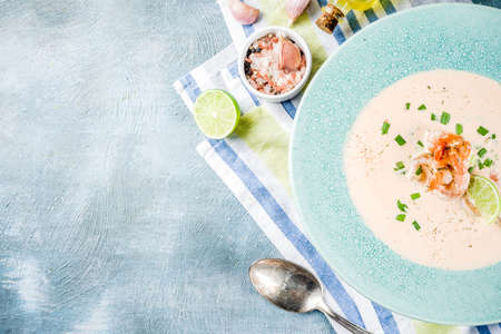 Mediterranean italian traditional food, homemade vegetable seafood creamy soup with shrimp prawns, lime and herbs, light blue concrete background copy space above
