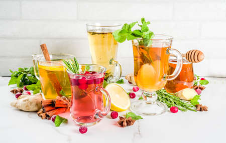 Various autumn winter herbal fruit and berry tea, with cranberry, mint, rosemary, lemon. lime. flowers, medical herbs and spices.
