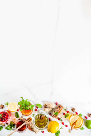 Various autumn winter herbal fruit and berry tea, with cranberry, mint, rosemary, lemon. lime. flowers, medical herbs and spices. top view copy space Stok Fotoğraf - 107860089