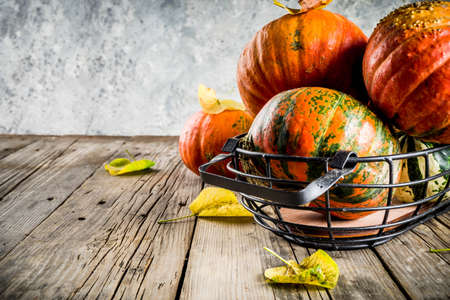 Autumn harvest concept, pumpkins background with yellow leaves, old rustic wooden table copy space