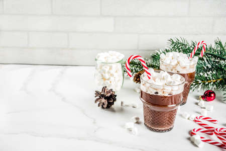 Peppermint hot chocolate with marshmallow and candy cane sweets in glass cups for Christmas holiday, white marble background copy space