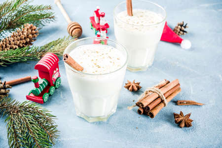 Traditional winter festive drink, sweet and spicy christmas eggnog cocktail in a glasses, on light blue background with xmas decorations, copy space.
