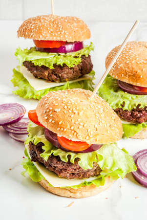 Fast food. Unhealthy food. Delicious Fresh Tasty Burgers with Beef Cutlet, fresh Vegetables and Cheese on white background. Copy space Stock Photo