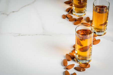 Golden almond liqueur with nuts on white marble background. copy space